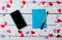 智能手机和蓝色纸片在一张白色木桌上的 库存图片