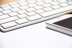 智能手机和键盘在桌上 免版税库存图片