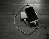 智能手机和powerbank在木背景 免版税图库摄影