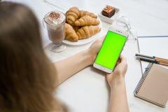 智能手机在一个绿色屏幕的手上在咖啡馆的,有色度钥匙绿色屏幕的巧妙的电话在白色背景,新技术 免版税图库摄影