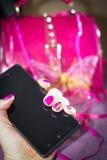黑智能手机在有明亮的辅助部件的女性手上 免版税图库摄影