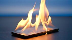 智能手机在蓝色背景的一张桌上烧 免版税库存照片