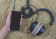 智能手机在黄麻绳索背景的耳机音乐 免版税图库摄影