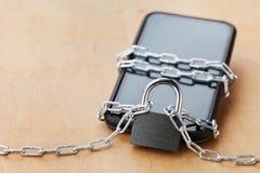智能手机栓了与锁的链子在木桌、小配件和数字式设备戒毒所概念上 免版税图库摄影