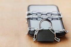 智能手机栓了与锁的链子在木桌、小配件和数字式设备戒毒所概念上 库存图片