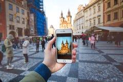 智能手机照片照相机和老布拉格集中与著名观光 有人的老城市广场在日落期间 免版税库存图片