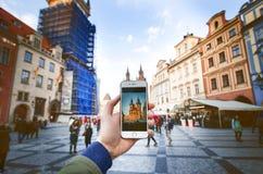 智能手机照片照相机和老布拉格集中与著名观光 有人的老城市广场在日落期间 免版税图库摄影
