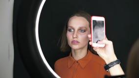 智能手机照相机的美好的式样妇女姿势在演播室 有构成面孔的,在softbox的短小金发肉欲的妇女 股票录像