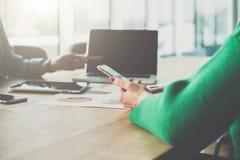 智能手机特写镜头在妇女` s手上 坐在桌和用途智能手机上的女实业家 免版税库存图片