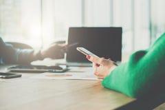 智能手机特写镜头在妇女` s手上 坐在桌和用途智能手机上的少妇 图库摄影