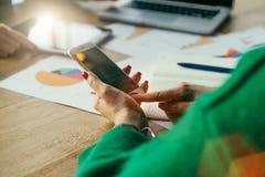 智能手机特写镜头在妇女` s手上 坐在桌和用途智能手机上的年轻女商人 免版税图库摄影