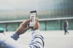 智能手机特写镜头有图表、图和图的在屏幕上在男性手上 库存照片