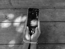 智能手机由更换者线的奴役胳膊 免版税库存图片