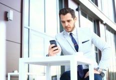 智能手机的人-年轻商人谈话在巧妙的电话 使用流动细胞的偶然都市专业商人 图库摄影