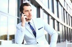 智能手机的人-年轻商人谈话在巧妙的电话 使用流动细胞的偶然都市专业商人 库存图片