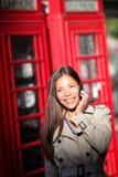 智能手机的伦敦妇女由红色电话亭 免版税图库摄影