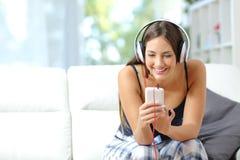 从智能手机的女孩听的音乐在家 库存图片