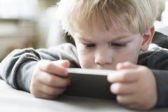 智能手机的小男孩 免版税库存图片