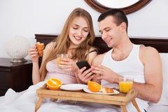 从智能手机的年轻宜人的微笑的夫妇读书新闻 免版税库存图片