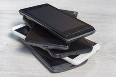智能手机被堆积在彼此顶部在柜台 库存图片