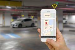 智能手机说明的被连接的汽车概念App显示事技术汽车通过IOT或互联网的停车处地点  免版税库存图片