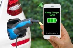智能手机说明的被连接的汽车概念App显示电池的状态被充电入电动车 库存图片