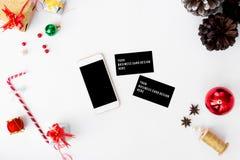 智能手机,圣诞节时间的名片构成 锥体和圣诞节装饰在白色背景 免版税库存照片
