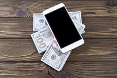 智能手机,盒在木背景的美元 免版税库存图片