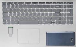 智能手机, usb在膝上型计算机键盘的闪光驱动 顶视图 现代设备和小配件 免版税库存照片