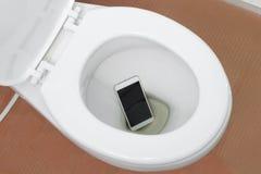 智能手机滴下了入洗手间 免版税库存图片