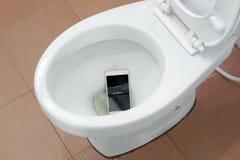 智能手机滴下了入洗手间 库存图片