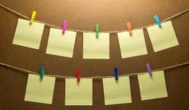晾衣绳垂悬九个岗位便条纸的照片 免版税库存图片