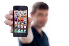 暂挂一新的iPhone 5的人 库存图片