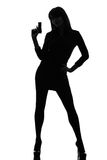 暂挂争取的性感的侦探妇女枪剪影 免版税库存图片