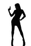暂挂争取的性感的侦探妇女枪剪影 免版税图库摄影