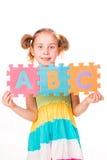 暂挂字母表的愉快的女孩在ABC上写字 免版税图库摄影
