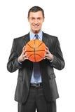 暂挂篮球的一个微笑的生意人 库存照片