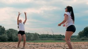 暑假、体育和人概念-有打在海滩的球的年轻女人排球 股票录像
