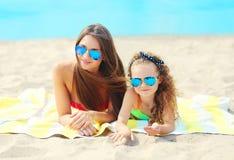 暑假、放松、说谎在海滩的旅行-画象母亲和孩子 免版税库存照片
