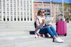 暑假、旅游业和旅行概念-带着旅游地图和手提箱的年轻女人-在台阶的拷贝空间 免版税图库摄影