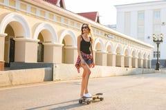 暑假、极端体育和人概念-在城市街道上的愉快的女孩骑马滑板 免版税图库摄影