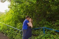 暑假、爱、浪漫史和人概念-拥抱愉快的微笑的年轻的夫妇户外 免版税库存照片