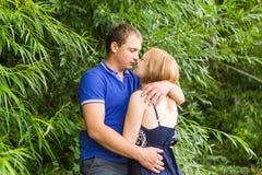 暑假、爱、浪漫史和人概念-拥抱愉快的微笑的年轻的夫妇户外 免版税库存图片