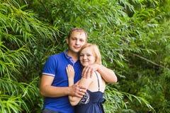 暑假、爱、浪漫史和人概念-拥抱愉快的微笑的年轻的夫妇户外 免版税图库摄影
