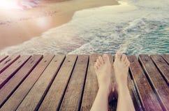 暑假与腿的概念背景在木码头 免版税库存图片