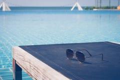 暑假和假日概念:太阳镜在游泳池在背景中投入了木沙发床有海景视图 库存照片