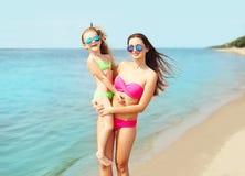 暑假和旅行-愉快的母亲和孩子泳装的在海滩 库存照片