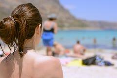 暑假妇女坐海滩享受看法 看海和Balos,希腊的拥挤海滩暑假 库存照片