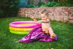 暑假题材 使用在一个房子的后院的一个小三岁的白种人男孩草的在圆的可膨胀的co附近 免版税库存图片