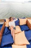 暑假,放松在游艇屋顶的愉快的妇女在日落 安达曼海泰国 库存照片